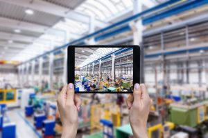 Horizontal color image of female hands holding a digital tablet in a modern plastic production line. Ordering on-line from injection moulding factory on a touchscreen tablet computer. Large factory, industrial machines, robots and manufacturing equipment arranged on clean and shiny flooring in background.